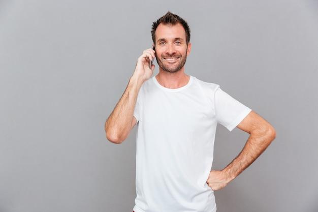 Glimlachende casual man praten aan de telefoon geïsoleerd op een grijze achtergrond