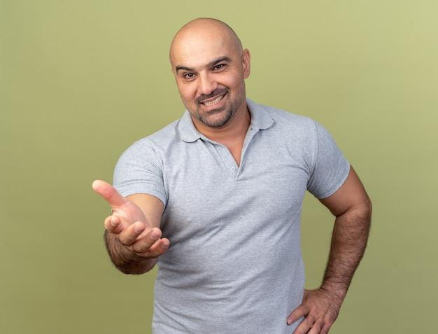 Glimlachende casual man van middelbare leeftijd die de hand op de taille houdt en de hand uitstrekt naar geïsoleerd op de olijfgroene muur
