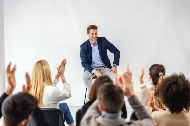 Glimlachende ceo die in directiekamer met zijn werknemers zit en toespraak houdt. werknemers klappen.