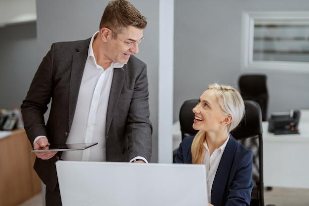 Glimlachende ceo op middelbare leeftijd in de tablet van de formele slijtageholding en sprekend aan zijn vrouwelijke werknemer. kantoor interieur. er is immers veel meer gezegd dan gedaan.