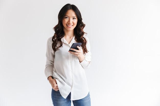 Glimlachende charmante aziatische vrouw die met lang donker haar zwarte celtelefoon houdt