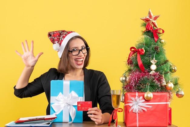 Glimlachende charmante dame in kostuum met de hoed van de kerstman en oogglazen die vijf tonen en gift en bankkaart in het bureau op geïsoleerd geel houden