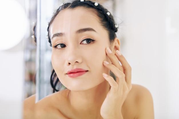 Glimlachende charmante jonge vietnamese vrouw die zichzelf in de spiegel bekijkt wanneer ze zich 's ochtends klaarmaakt