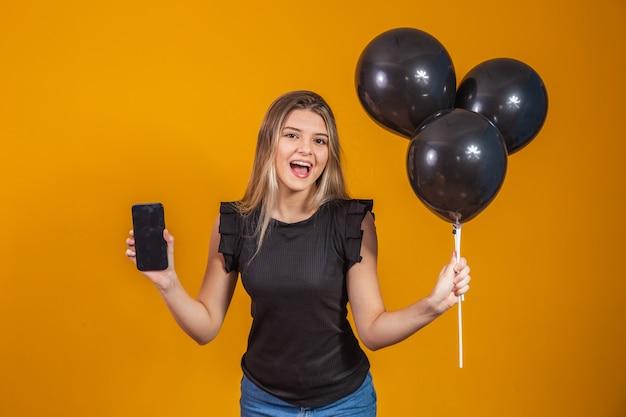 Glimlachende charmante jonge vrouw met een mobiele telefoon met leeg leeg scherm op gele achtergrond met luchtballonnen studio portret. black friday-afrekening
