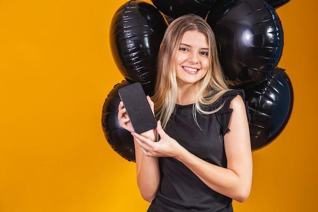 Glimlachende charmante jonge vrouw met mobiele telefoon met leeg leeg scherm op gele achtergrond met luchtballonnen studio portret. zwarte vrijdag verkoop