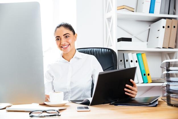 Glimlachende charmante zakenvrouw die documenten vasthoudt en naar het computerscherm kijkt terwijl ze aan het bureau zit