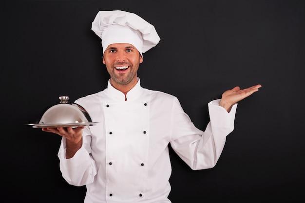 Glimlachende chef-kok aanbevolen hoofdgerecht