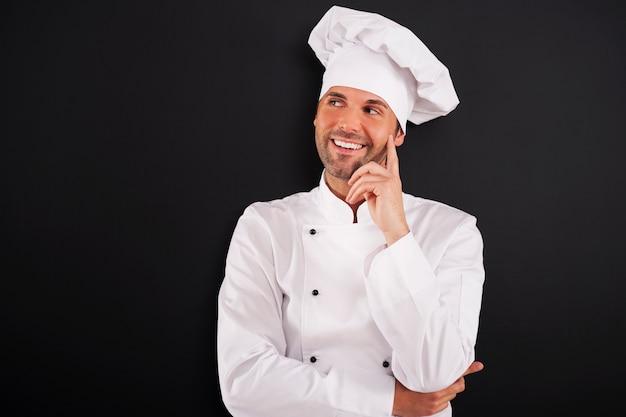 Glimlachende chef-kok die aan de kant kijkt