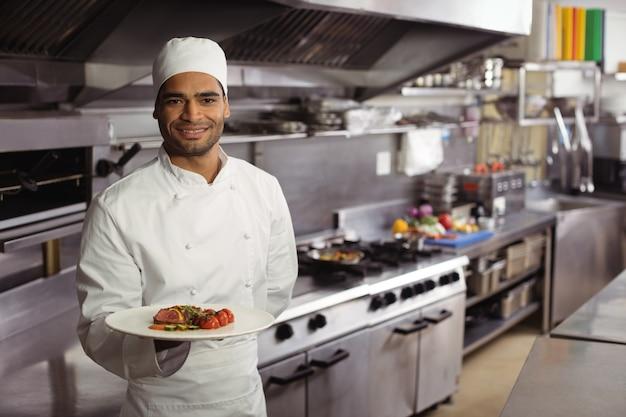 Glimlachende chef-kok die heerlijke schotel in keuken houdt