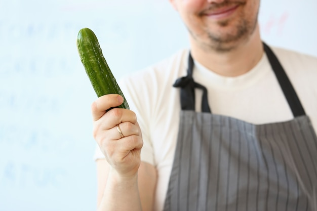 Glimlachende chef-kok holding raw green organic komkommer