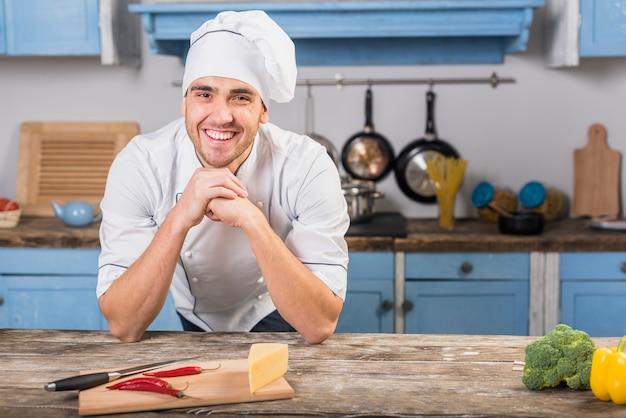 Glimlachende chef-kok in de keuken