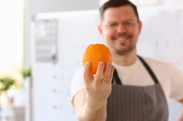 Glimlachende chef-kok met oranje ingrediënt.