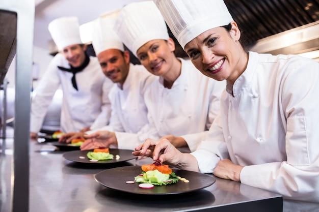 Glimlachende chef-kok terwijl het verfraaien van voedselplaat
