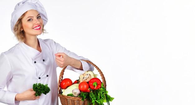 Glimlachende chef-kokvrouw met mandgroente. professionele kok met mand met verse groenten. biologisch voedselconcept.
