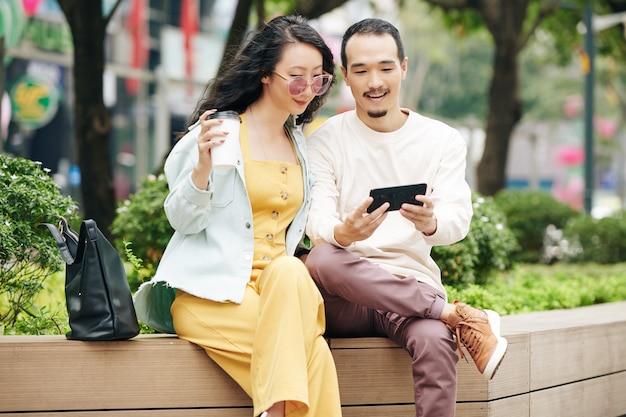 Glimlachende chinese jongeman die foto of video op het smartphonescherm laat zien aan een mooie vriendin wanneer ze op een bankje in het park zitten