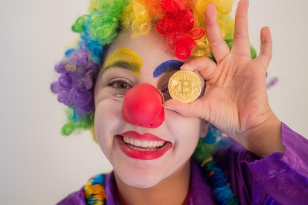 Glimlachende clown die een bitcoin-muntstuk in de richting van zijn ogen houdt