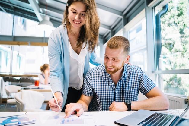 Glimlachende collega's die nota's van plannen maken
