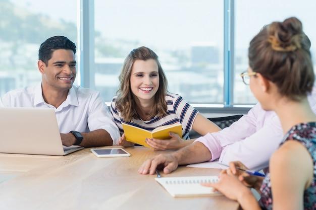 Glimlachende collega's die tijdens vergadering met elkaar in wisselwerking staan