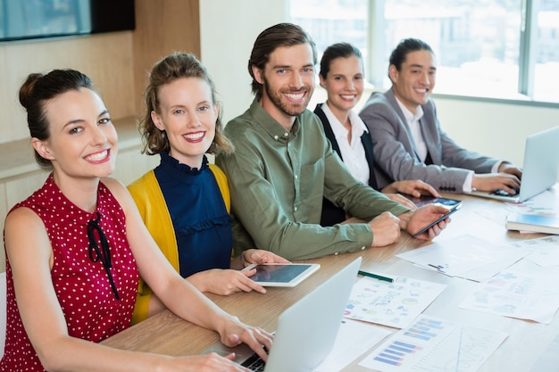 Glimlachende commerciële teamzitting in conferentieruimte