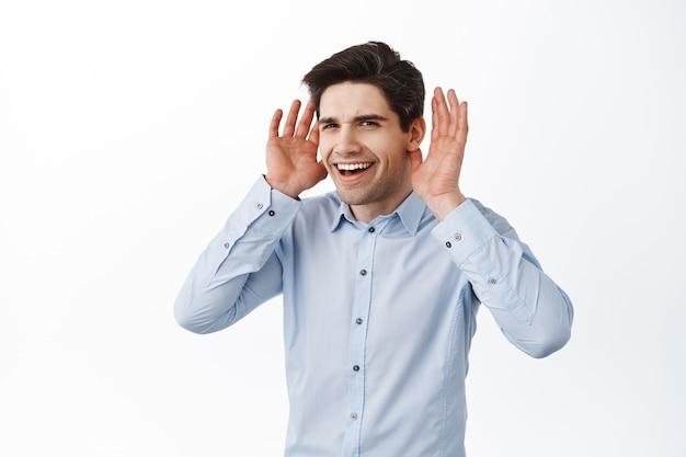 Glimlachende corporate ceo man houdt handen in de buurt van oren en kijkt geïntrigeerd, luistert beter, kan je niet horen, niet bereid om te luisteren, staande over een witte muur