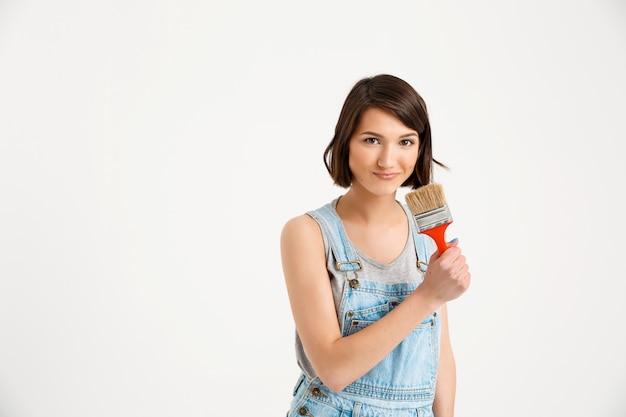Glimlachende creatieve vrouw met het schilderen van borstel