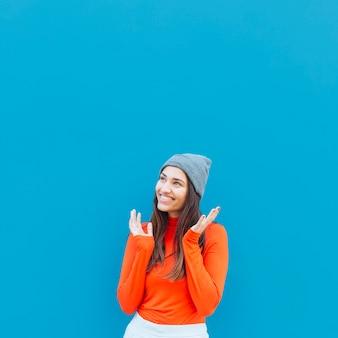 Glimlachende dag dromende vrouw die weg tegen blauwe achtergrond kijken