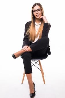 Glimlachende dame die in glazen op een zwarte stoel op wit zit