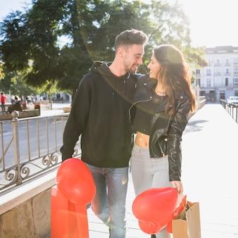 Glimlachende dame die jonge gelukkige kerel met pakketten en ballons op straat omhelzen