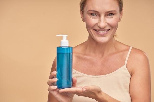 Glimlachende dame die micellair water in fles in studio houdt