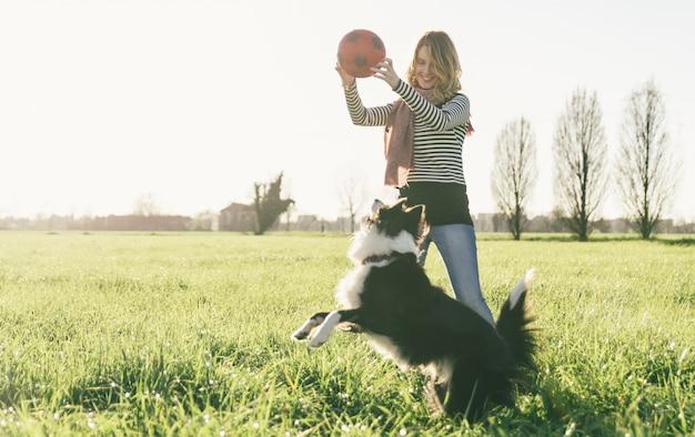 Glimlachende dame die vrije tijd met haar hond neemt