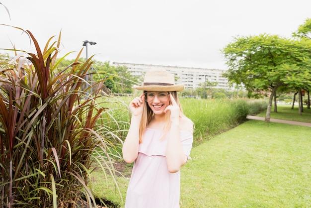 Glimlachende dame in oogglazen en hoed dichtbij hoog gras in park