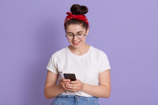 Glimlachende dame met donker haar en knoop die slimme telefoon in handen houdt en bericht van vriend leest, ziet er gelukkig uit, vrijetijdskleding draagt