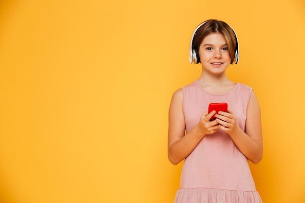 Glimlachende dame met hoofdtelefoons en smartphoe die geïsoleerde camera kijken