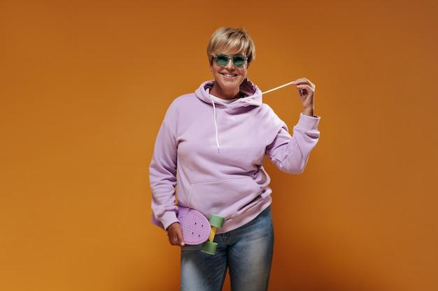 Glimlachende dame met kort haar en moderne bril in roze sweatshirt en coole spijkerbroek poseren met modern skateboard op oranje achtergrond.