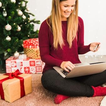 Glimlachende dame met laptop en plastic kaart in de buurt van geschenkdozen en kerstboom