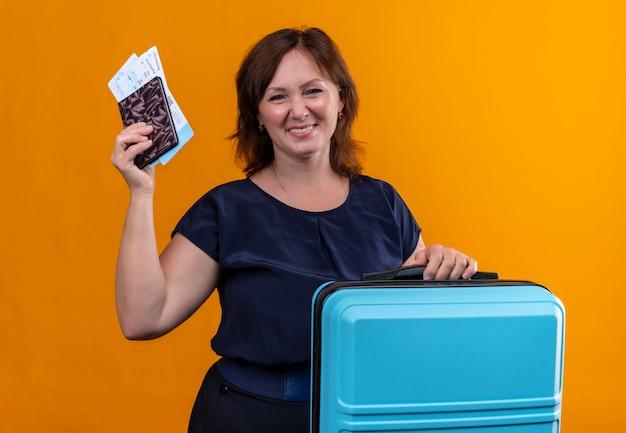 Glimlachende de holdingskoffer en kaartjes van de reizigersvrouw op middelbare leeftijd met portefeuille op geïsoleerde sinaasappel