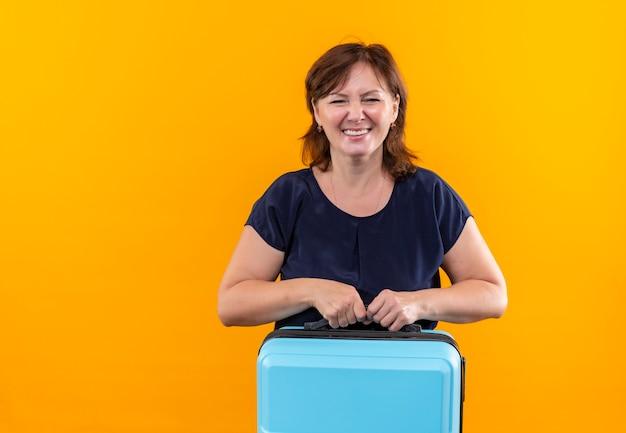 Glimlachende de holdingskoffer van de reizigersvrouw op middelbare leeftijd op geïsoleerd geel