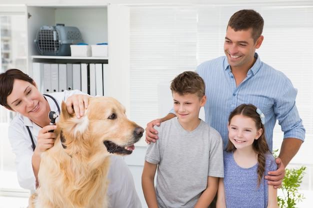 Glimlachende dierenarts die een hond met zijn eigenaars onderzoekt