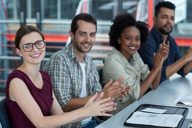 Glimlachende directeuren die in vergadering op kantoor slaan