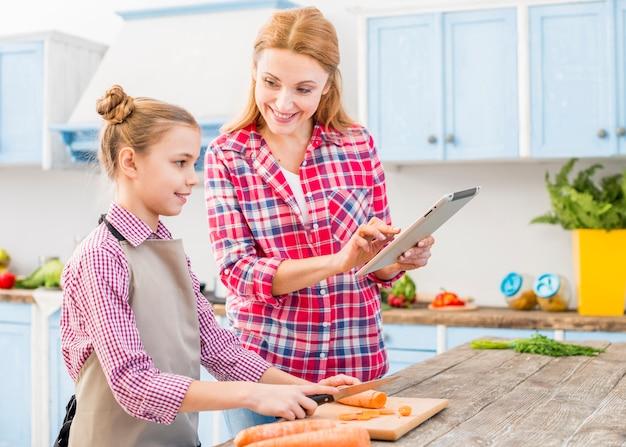 Glimlachende dochter die haar moeder bekijkt die recept op mobiele telefoon toont