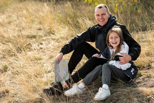 Glimlachende dochter en vader die fotograaf bekijken
