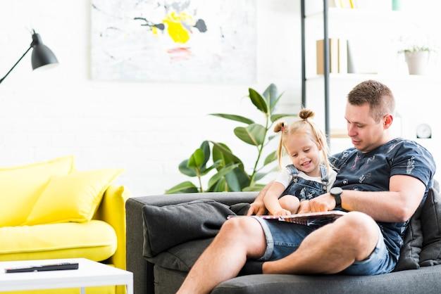 Glimlachende dochter en vader die in boek kijken