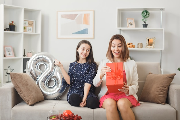 Glimlachende dochter geeft cadeau aan verraste moeder op gelukkige vrouwendag zittend op de bank in de woonkamer