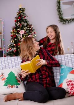 Glimlachende dochter houdt een snoepriet vast en kijkt naar haar moeder die een boek leest terwijl ze op de bank zit en thuis geniet van de kersttijd