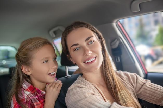 Glimlachende dochter in gesprek met haar moeder vanaf de achterbank van de auto