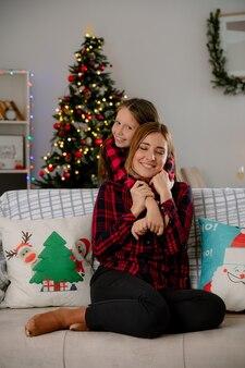 Glimlachende dochter knuffels moeder zittend op de bank van achteren en genieten van kersttijd thuis