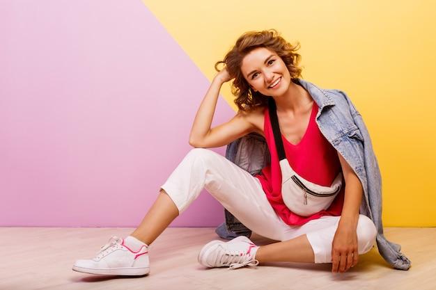Glimlachende donkerbruine mooie vrouw die modieuze sportieve uitrusting en jeansjasjezitting op de vloer draagt.