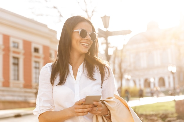 Glimlachende donkerbruine vrouw die in overhemd en zonnebril smartphone houdt