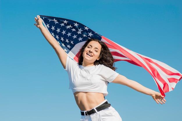 Glimlachende donkerbruine vrouw die in witte kleren de grote vlag van de vs houden