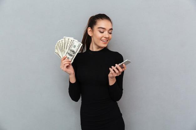 Glimlachende donkerbruine vrouw die in zwarte kleren geld houdt